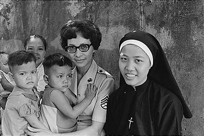 A Woman Marine Staff Sergeant helps with caring for orphans in Saigon